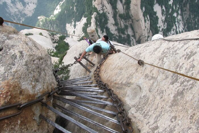 People climbing iron rods planted by monks for easy accessibility to the top