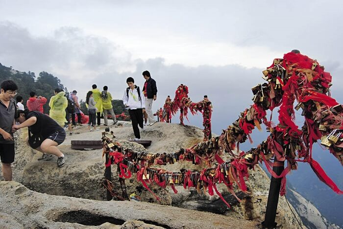 People tying religious flags at the top of Mount Huashan