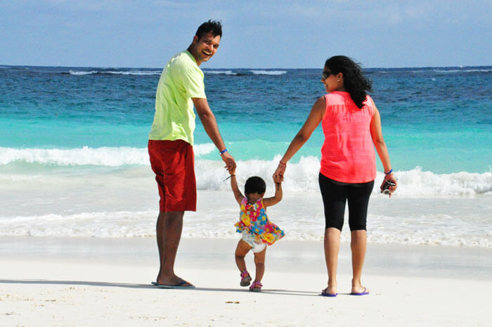 A couple walking on the shore with their tiny tot