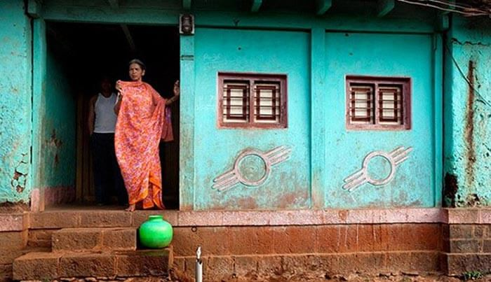 A woman looks outside her doorless house at Shani Shingnapur