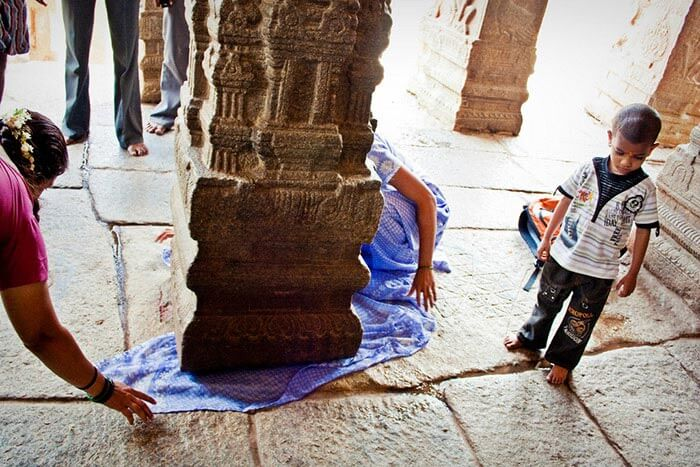 People passing objects under the hanging pillar at Lepakshi