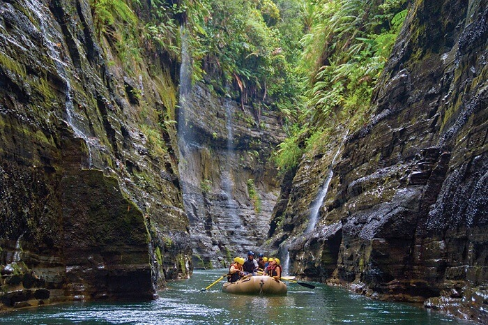Tourists slicing a deep chasm through the Upper Navua River while kayaking in Fiji