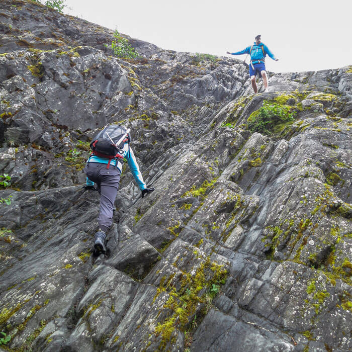 Trekkers rappelling a slippery mountain before reaching the ice cave