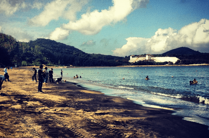 Tourists enjoying at the unique black sand beach of Macau