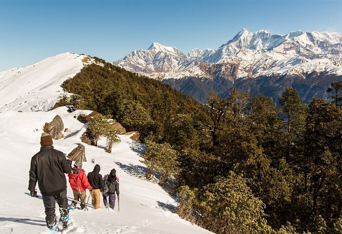 A small group of trekkers on their trek to Brahmatal with Mt Trishul and Mt Ghunti in the backdrop