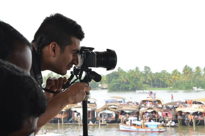 A photographer takes a photo during snake boat race practice session