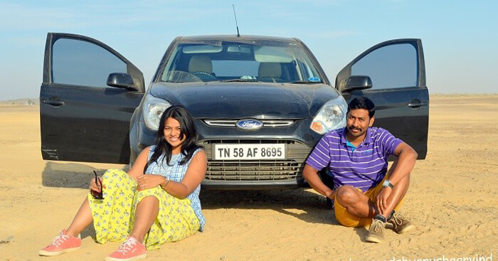 Anusha and Arvind sit outside a Ford Figo in the desert of Pakistan