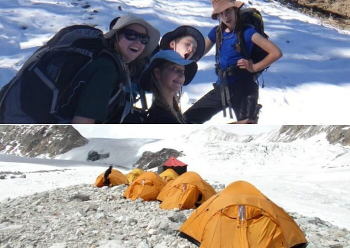 Girls pose for a picture while others set up tents on the Auli Gorson winter trek