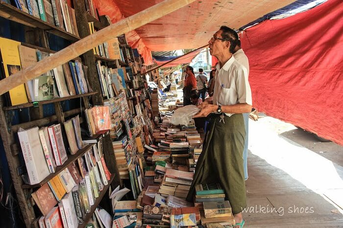 An old looks at the books displayed on the streets of Myanmar