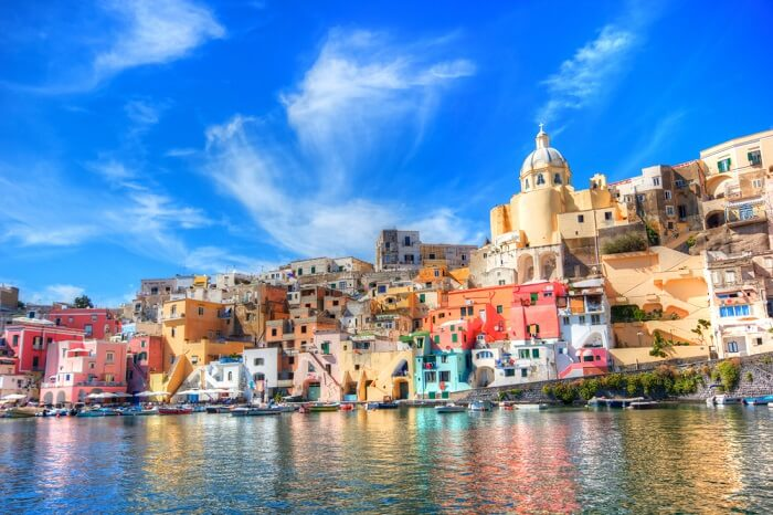 Boats lined up against the shore of the colorful city of Naples