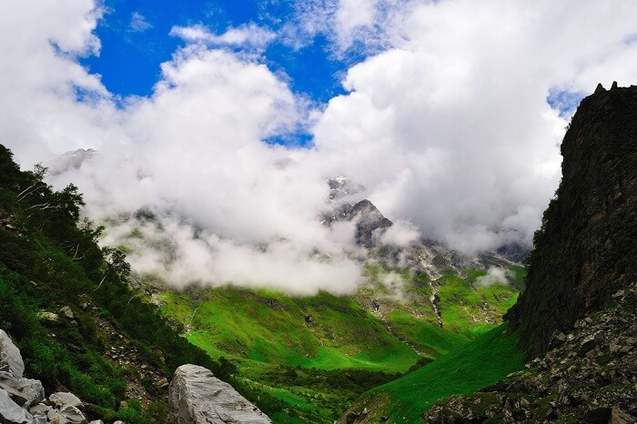The clouds flowing across the green hills at the Valley of Flowers