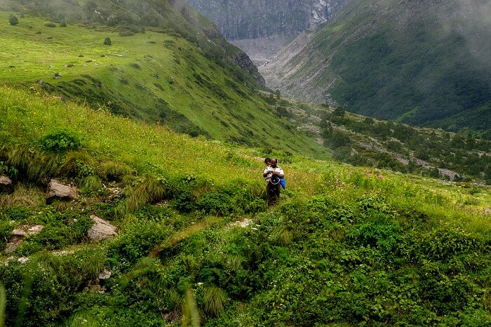 Locals walk through the Valley of Flowers