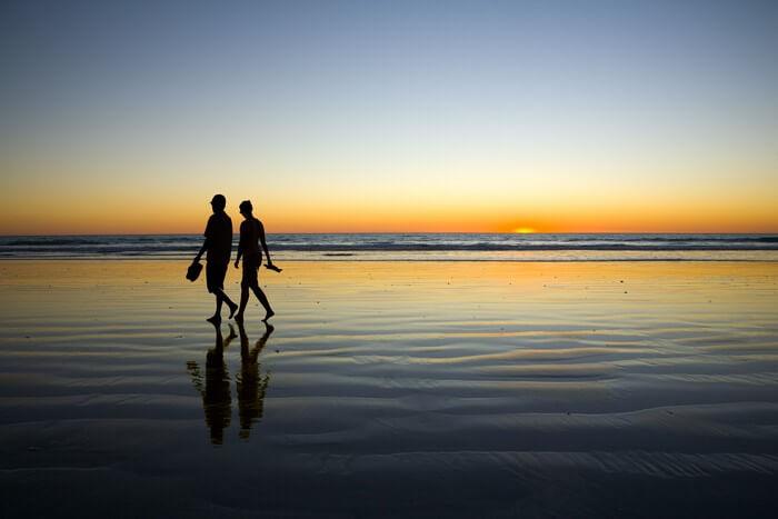 Couple walk by the Besant Nagar Beach while the sun sets