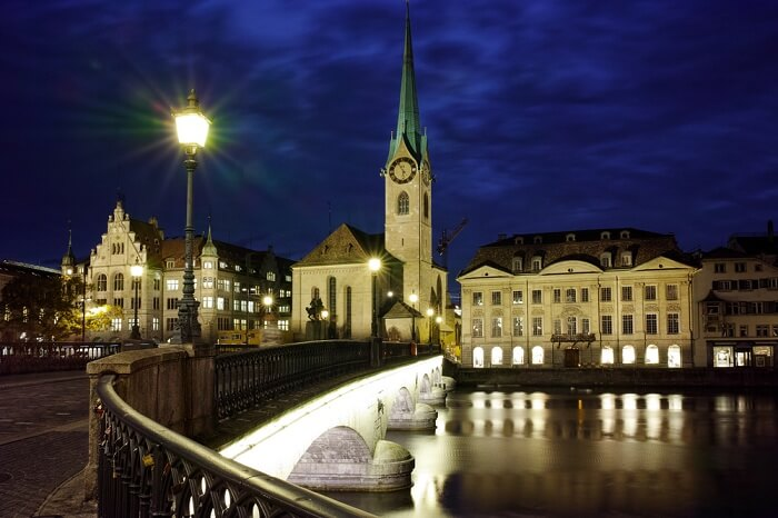 Night photo of Fraumunster Church and bridge over Limmat River