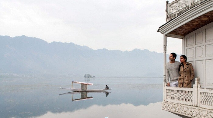 Couple enjoying unspoiled views of Dal Lake while staying in houseboat
