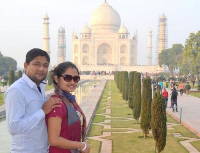 Madhumita and her husband pose in the background of Taj Mahal