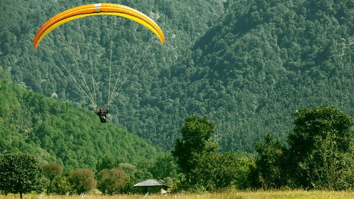 A paraglider lands down amidst the green hills of Bir Billing