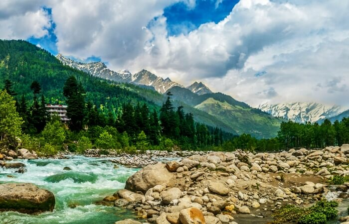 The flowing Beas river with the snow-capped hills in the backdrop at Manali