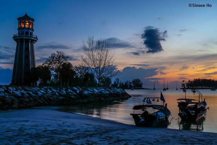 Boats dock at the Pantai Kok beach near the grand lighthouse as the sun sets into the sea