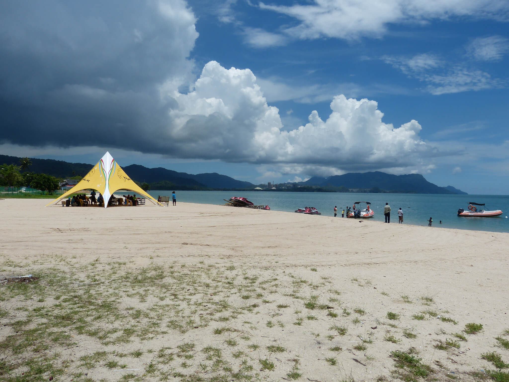 Tourists wait in a tent at Tanjung Rhu Beach for their turn to take a speed boat ride in the sea