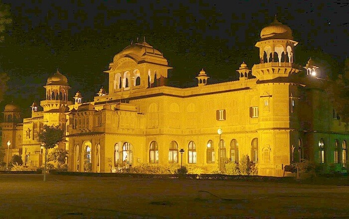 A well-lit entrance of the Lalgarh Palace at night