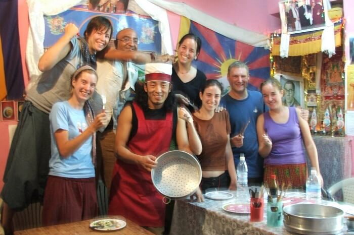 Tourists pose with the cook and trainer at the Sangey Kitchen