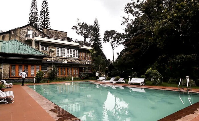 The pool-side area overlooking the victorian facade of Aranya Nivas Resort in Thekkady