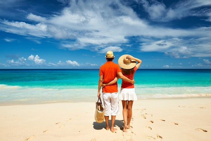 Couple relaxing on a tropical beach Anse Intendance at Mahé in Seychelles
