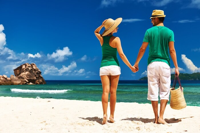 Couple relaxing on a tropical beach Anse Source d'Argent at La Digue in Seychelles