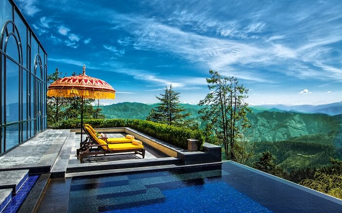 Outdoor pool offering picturesque views of valleys around Wildflower Resort in Shimla
