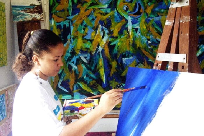 Rita Morel painting at her gallery in Seychelles