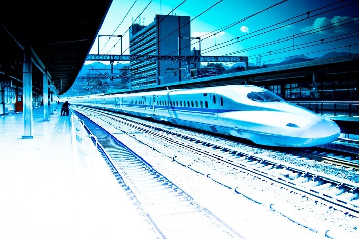 A bullet train whizzes pass a station
