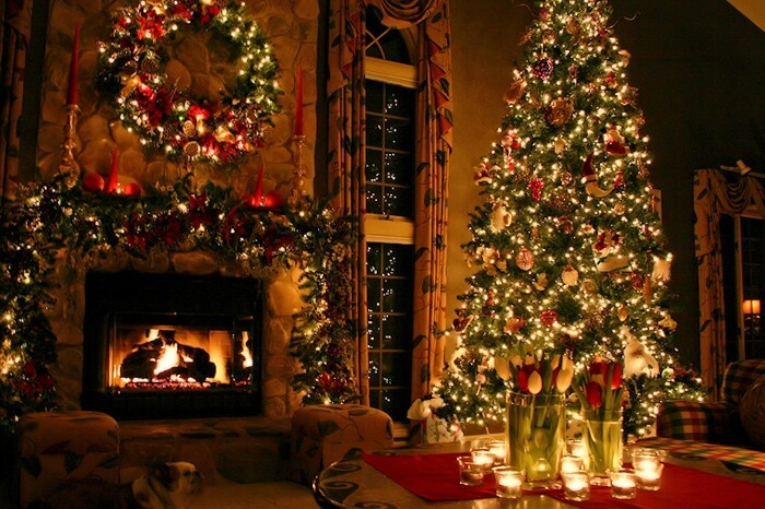 A shot of a decorated Christmas tree by the side of a fireplace in a house