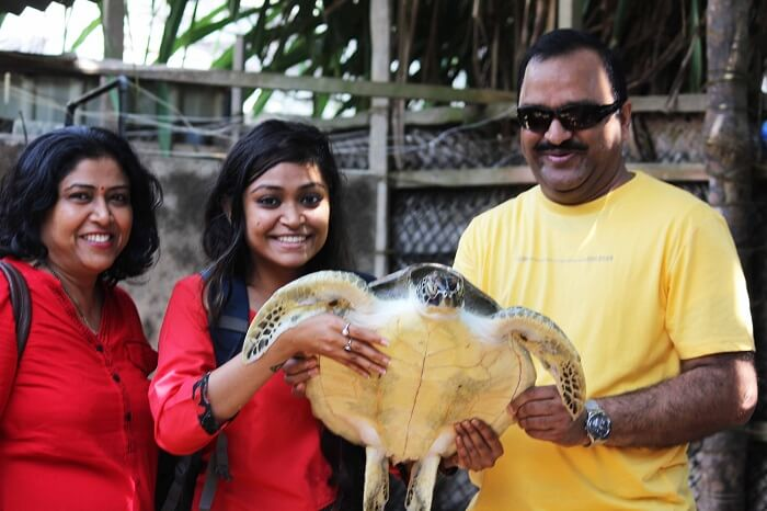 Kanika and her father with a turtle