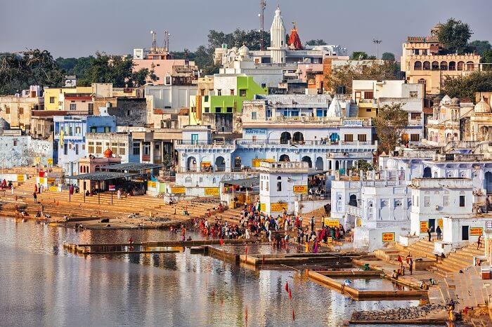 Hindu devotees pilgrims bathing in sacred Puskhar lake on ghats of Pushkar