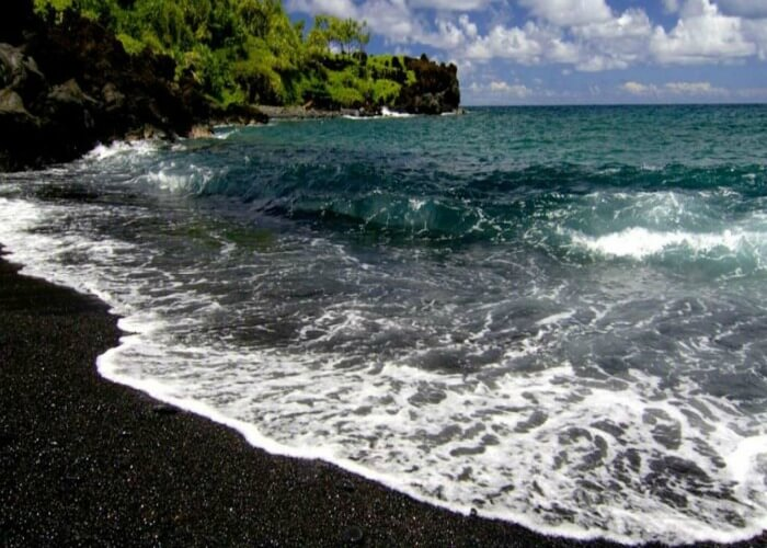 Have a view of the black sand amidst the crystal clear waters