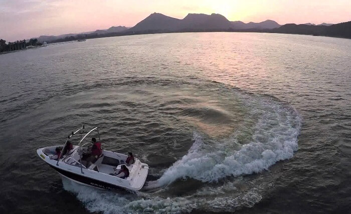 A couple of tourists enjoying the thrills of motor boating in Rajasthan at Fateh Sagar Lake