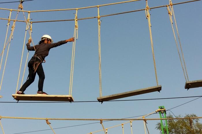 Adventurer performing plank walk at Rope Castle Adventure Park