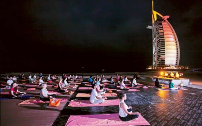 Participants performing Yoga at night with Burj Al Arab in the backdrop