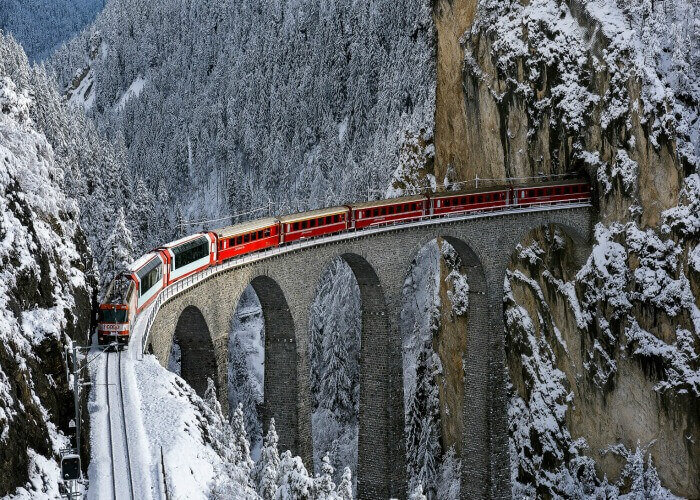 The Glacier Express passing over a bridge through scenic snowy landscapes
