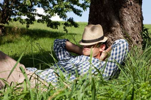 man sleeps under a tree