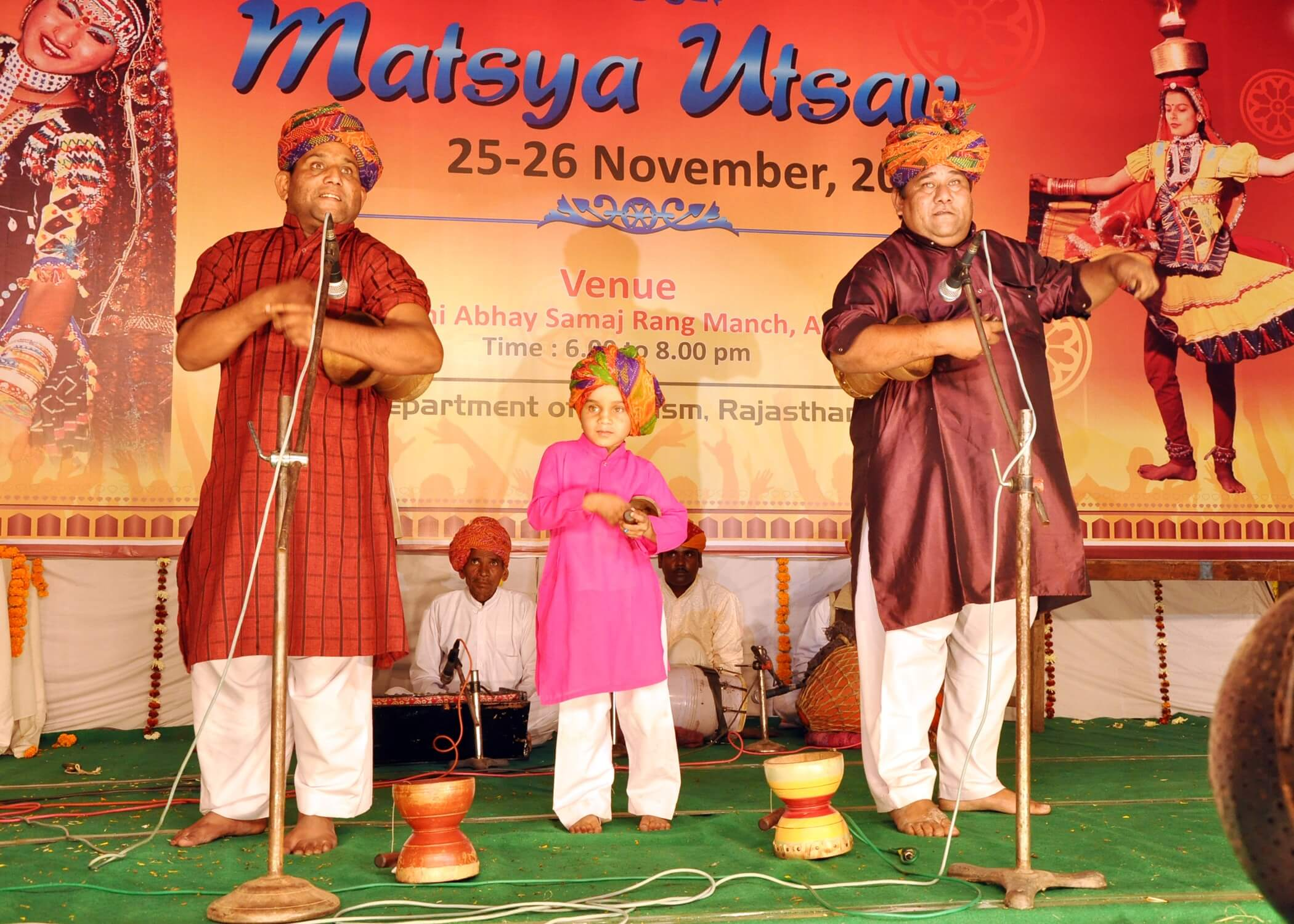 two men and a kid performing in Alwar