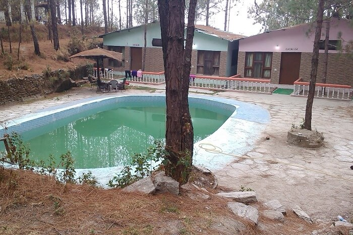 The swimming pool and cottages at the Retreat Anand Jungle Resort in Lansdowne