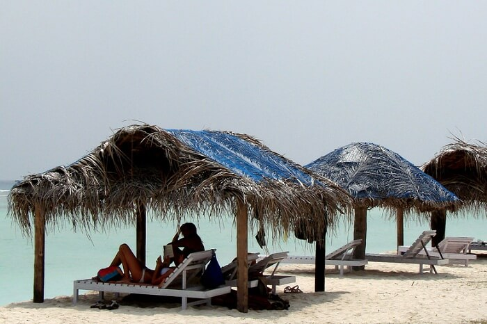A couple relaxes at the huts on the Kadmat Beach in Lakshadweep