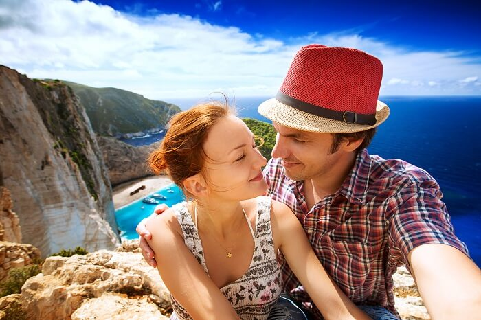 A honeymoon couple in Zakynthos with the Navagio Beach or Shipwreck Beach in the background