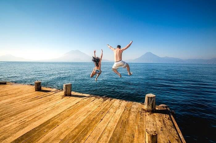 A honeymoon couple jumping into the at lake Atitlán in Panajachel