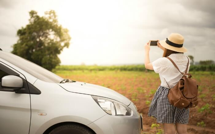 A woman clicking pictures on her road journey