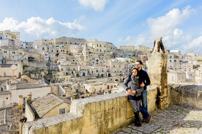 Attractive couple enjoying view of Matera old town of Southern Italy on a beautiful sunny day