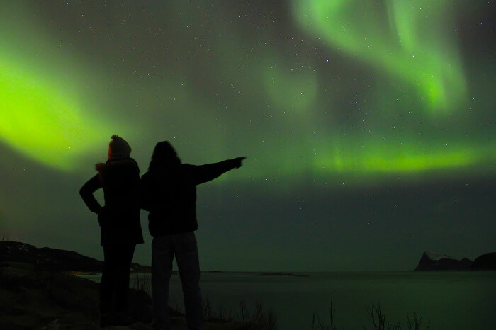 Couple braving the cold to watch the Northern lights in Lapland