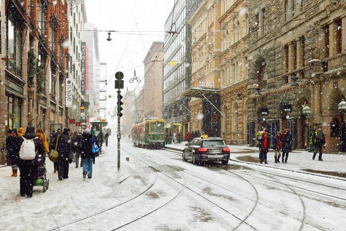 A treetway in Finland with cars and a tram passing through